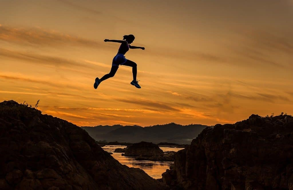 female athlete leaping in air dusk