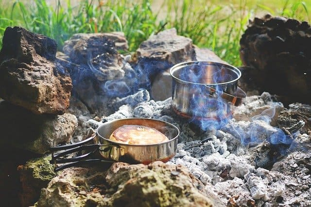 pots cooking on campfire coals