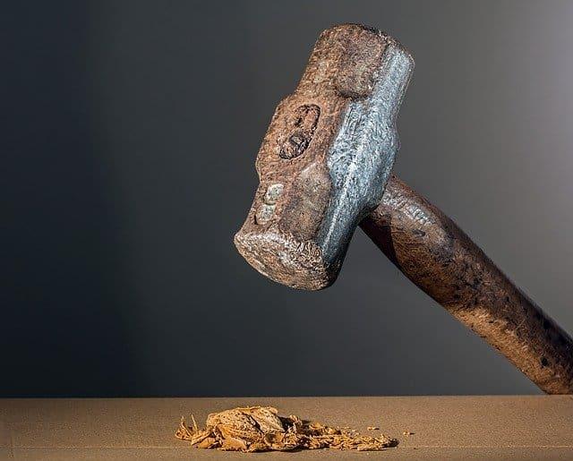 sledge hammer crushing walnut
