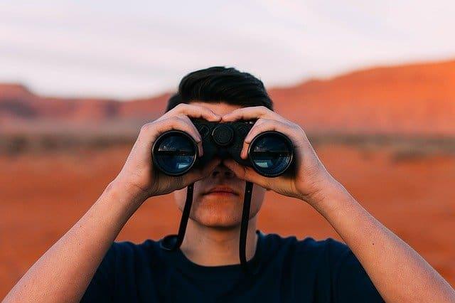observant man looking thru binoculars